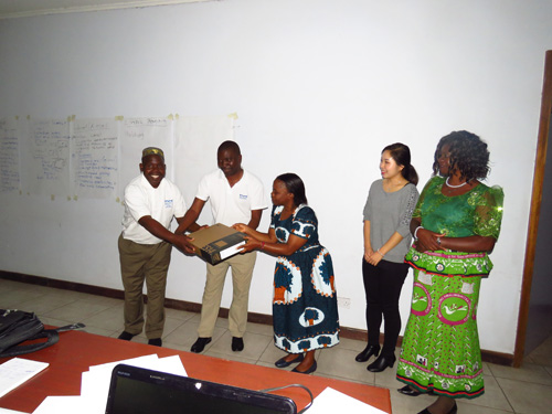 Director of Community Development, Mrs. Sawasawa (middle) presenting a donation of a laptop computer to Village Head Mlima (far left) and Village Head Mponda.